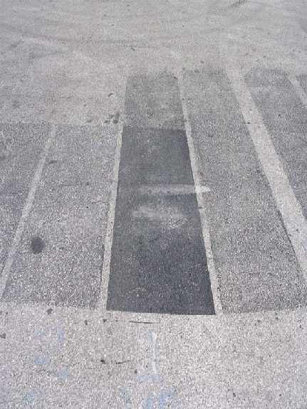 Test strips of polymer modified asphalt-based pavement sealer and refined coal tar-based pavement sealer February 2010. Note that the refined tar-based sealer is still present while the asphalt based product had almost completely worn off